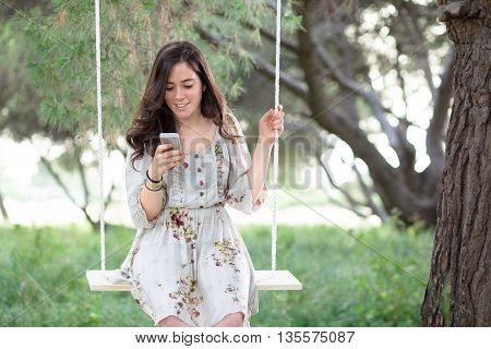 Woman with Smartphone on a Swing in a Park