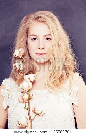 Woman with long blond curly hair on dark