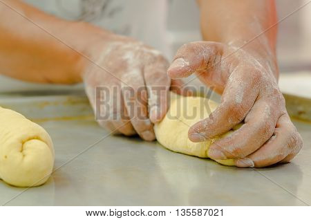Hands of baker working, kneading and rolling bread dough, shaping into loaf before cooking.