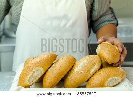 Pile of fresh bread loafs, baker standing behind with only apren and arms visible, bakery concept.