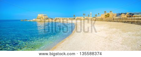 The comfortable sand beach with the luxury view on the ancient ruins of the Roman city of Caesarea Israel.