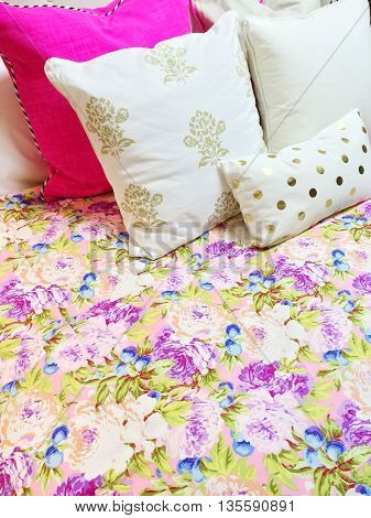 Bed with colorful floral design bedclothes and lots of pillows.