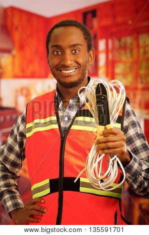 Young electrical worker wearing safety vest, holding cables and cable pliars, smiling with great positive attitude.