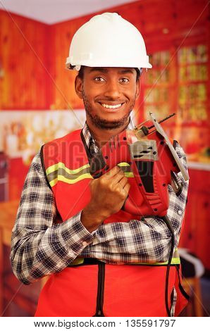 Young engineer carpenter wearing square pattern flanel shirt with red safety vest, holding jigsaw smiling to camera.