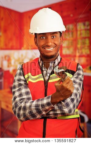 Young engineer carpenter wearing helmet, square pattern flanel shirt with red safety vest, holding small handheld electric saw smiling to camera.
