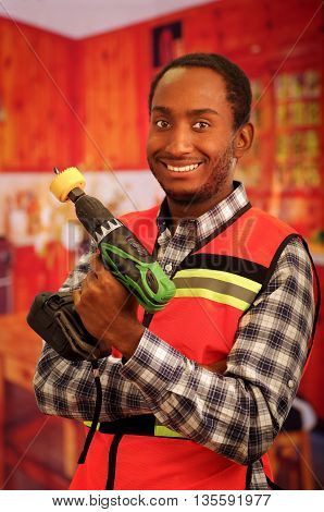 Young engineer carpenter wearing square pattern flanel shirt with red safety vest, holding handheld electric power drill smiling to camera.