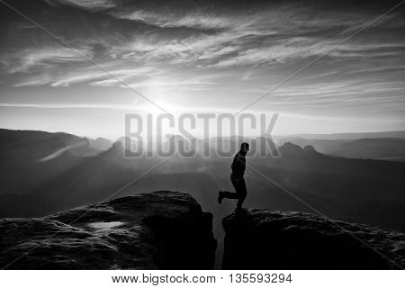 Happy Man  Jumping Between Rocks, Misty Mountains.