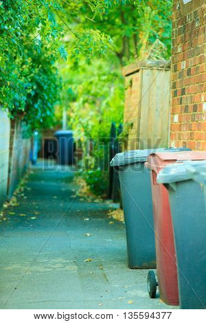 Row of plastic wheely bins in the street outside houses in England