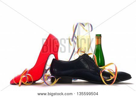 ladies red high heels and black men's shoes with champagne and streamers concept for gender topics such as party dating flirting love affair isolated with shadows on a white background