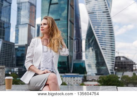 Young woman sitting against office buidings. Coffee break, lunch concept.