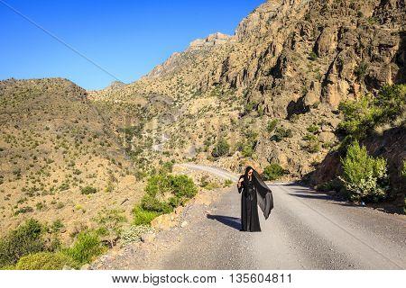 Woman in black abaya is walking on a road in Al Hajar Mountains in Oman