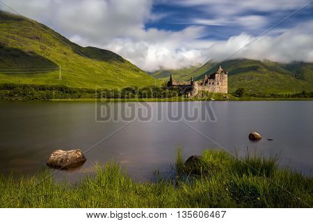 Stones in Loch Awe with Kilchurn Castle an mountains in background Highlands Scotland