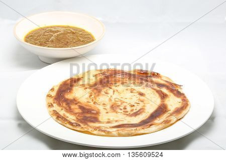 Plain Ghee Fried Paratha with curry dal on plate and bowl white background