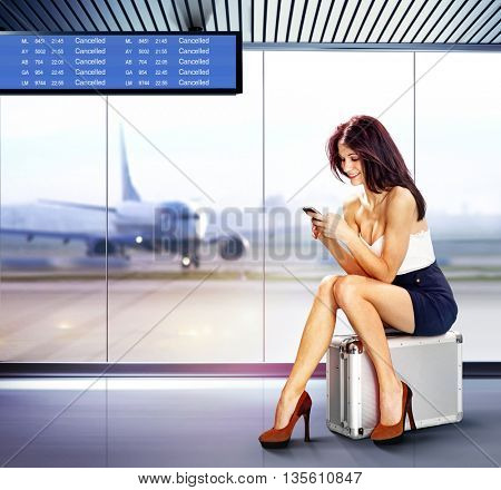 beautiful traveler with mobile phone in airport