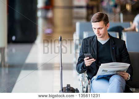 Man passenger in an airport lounge waiting for flight aircraft