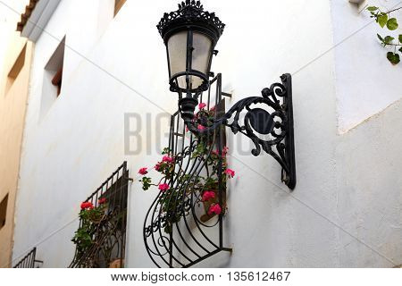Benidorm white facade window with flowers pot and streetlight Mediterranean