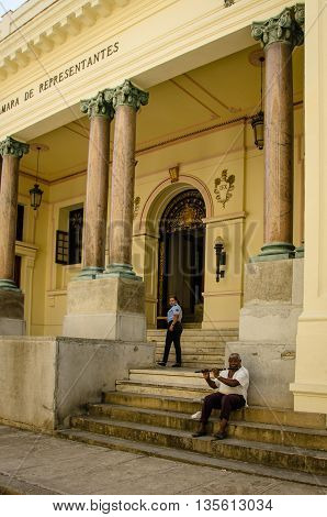 HAVANA - CUBA JUNE 19, 2016: An old man, sitting on the steps of a historic building in La Habana Vieja, plays a flute to supplement his meager pension from the Cuban government.
