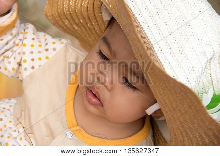 cute Infant with big Straw hat posing