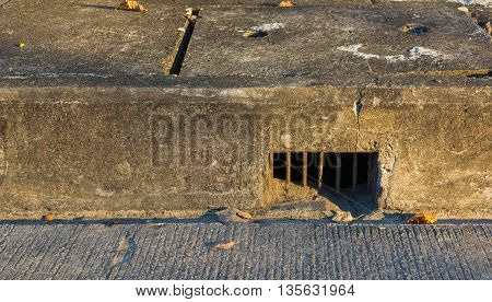 image of drain hole at sidewalk of street on day time .