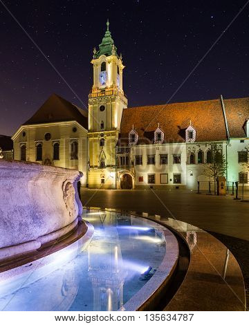 Old Town Hall in Bratislava Slovakia at night with part of Maximilians Fountain in the foreground.