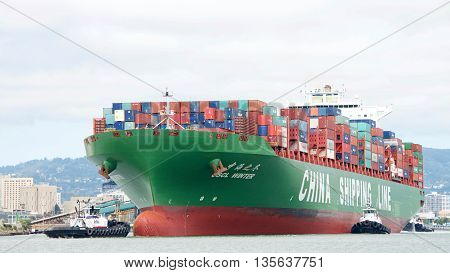 Oakland CA - June 09 2016: Tugboats assist cargo ship CSCL WINTER to maneuver into the Port of Oakland the fifth busiest port in the United States.