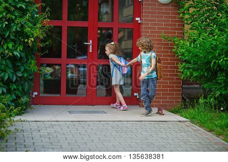 Two pupils of elementary school on a schoolyard. The boy holds the schoolmate by a hand. And the little girl with curiosity looks at a glass door of school.