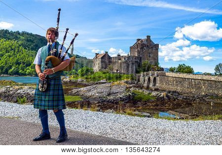 Lochash Scotland - June 20 2012: Highlands a bagpipe player and the Eilean Conan castle in background.