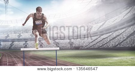 Sportsman practising hurdles against view of a stadium