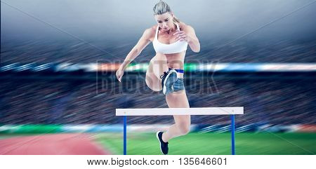 Female athlete jumping against view of a stadium