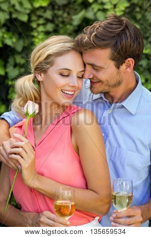Happy couple embracing while holding wineglasses at front yard