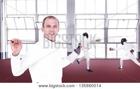 Swordsman holding fencing sword against gym
