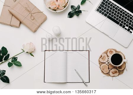Workspace with opended diary laptop rose coffee on white background
