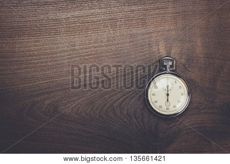 stopwatch on the brown wooden table background