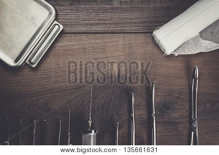 surgical armaments on the dark brown wooden background