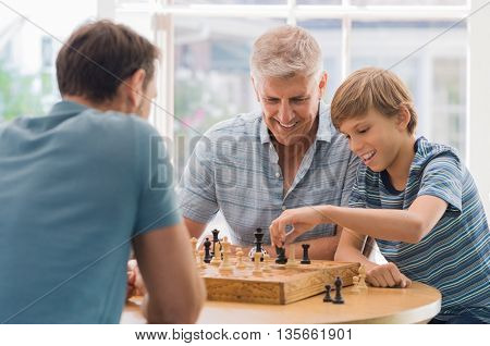 Grandfather teaching grandson how to play chess. Father and son playing chess with grandchild. Grandfather watching son and grandson playing board game at home. poster