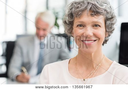 Portrait of smiling senior businesswoman looking at camera. Close up face of happy mature business woman smiling at office. Successful business woman with senior businessman working in background.
