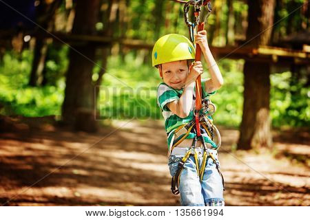 Adventure climbing high wire park - little child on course in mountain helmet and safety equipment.