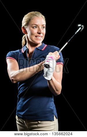 Golf player about to swing a golf ball on black background