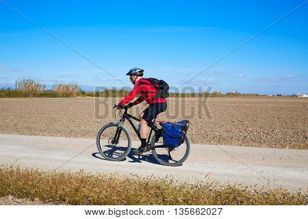 Biker MTB cycle tourism with panniers in Albufera of valencia spain