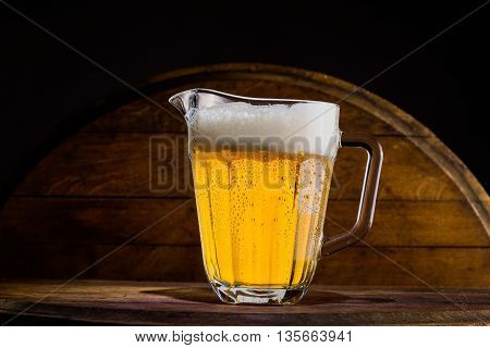 Pitcher of beer on ice, wood background