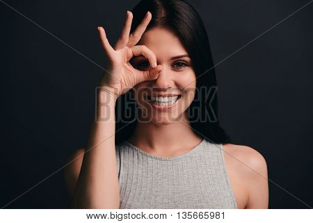 Just for fun. Beautiful young woman gesturing ok sign near her eye and smiling while standing against grey background