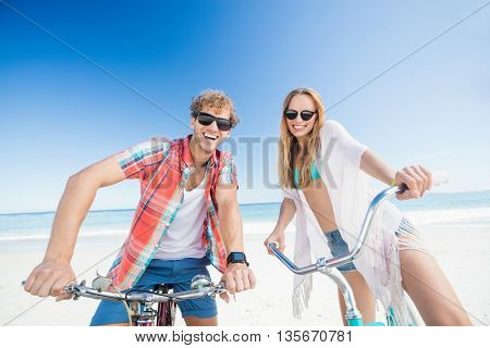 Couple posing with bike on the beach on a sunny day