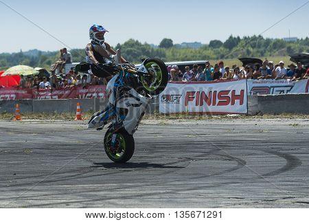 VinnytsiaUkraine-July 25 2015: Unknown stunt biker entertain the audience before the start of the championship of drifting on July 252015 in Vinnytsia Ukraine.