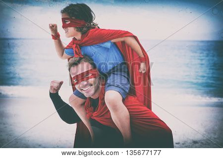 Happy father and son in superhero costume pretending to run at beach