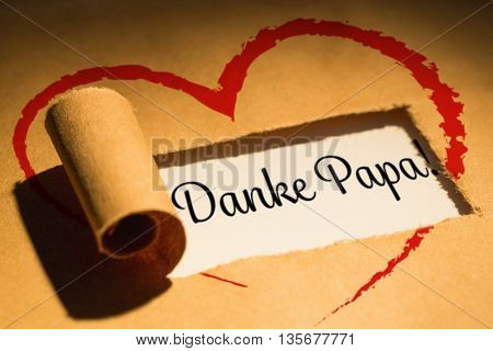 Word danke papa against directly above shot of torn brown paper