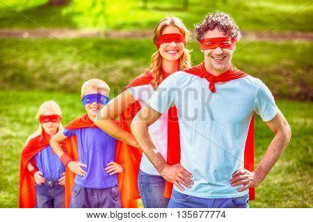 Happy family pretending to be superhero in the park