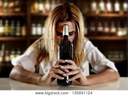 drunk blond woman alone in wasted depressed expression looking thoughtful and sad holding red wine bottle against her forehead at bar or pub in alcohol abuse and alcoholic housewife concept