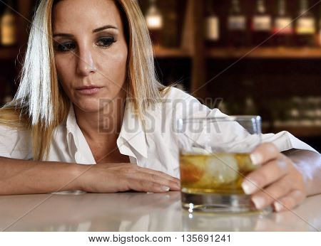 drunk woman alone in wasted and depressed face expression holding and looking thoughtful to scotch whiskey glass isolated at bar or pub in alcohol abuse and alcoholic housewife concept