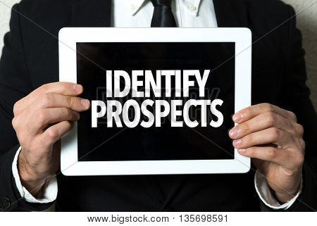 Business man holding tablet with the text: Identify Prospects