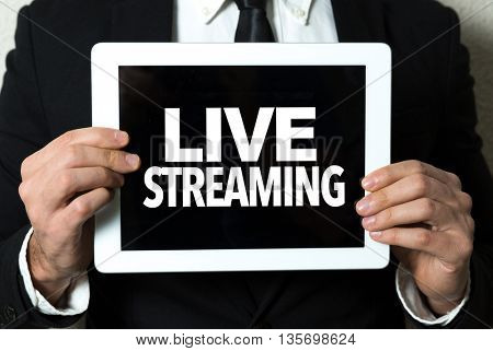 Business man holding tablet with the text: Live Streaming